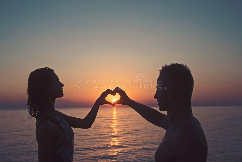 Женщина и человек с водой рук сердца на море в заходе солнца Летние отпуска и каникулы перемещения День семьи и валентинок стоковые изображения rf