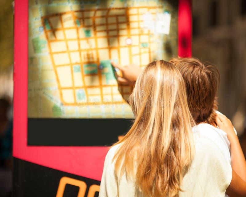 Женщина и человек наблюдая карту на улице стоковое фото rf