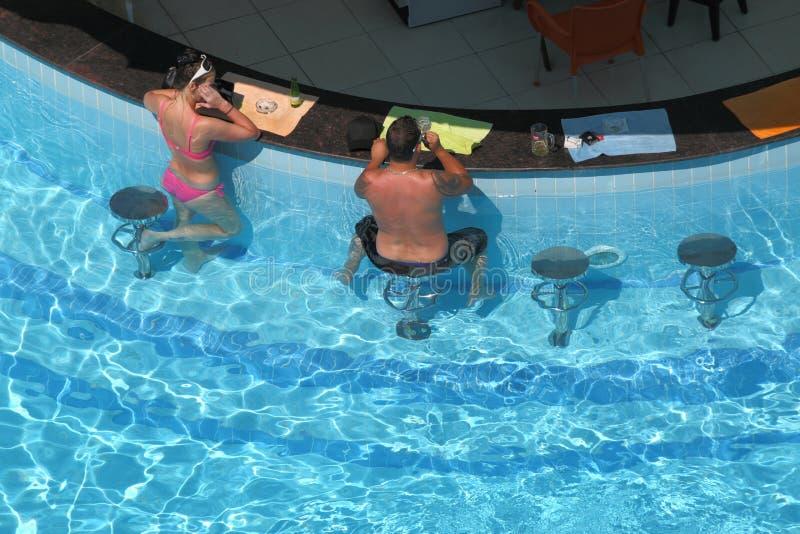 Женщина и человек сидя на адвокатском сословии бассейном стоковое изображение