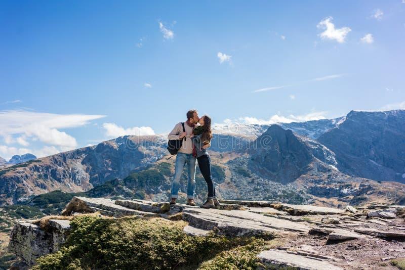 Женщина и человек целуя любяще пока пеший туризм горы стоковые изображения rf