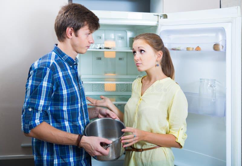 Женщина и человек Frustraited голодая около холодильника без любой еды стоковое фото
