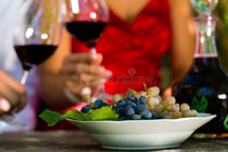 Женщина и человек в вине виноградника выпивая стоковые фотографии rf