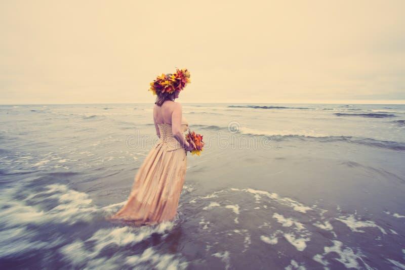 Женщина идя в воду в осени стоковые изображения