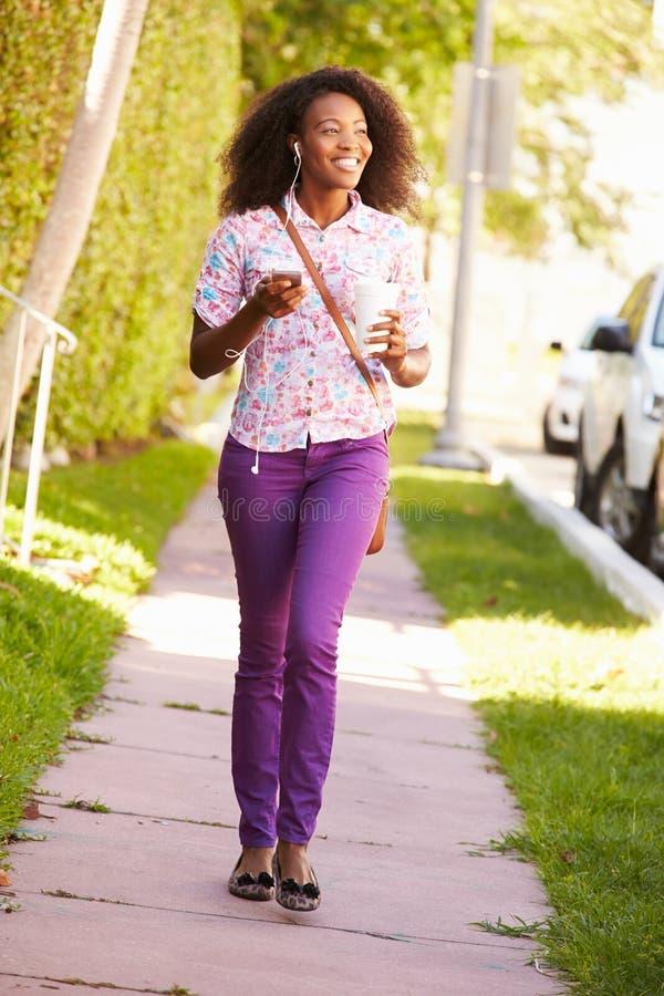 Женщина идя вдоль улицы для работы слушать к музыке стоковые фото