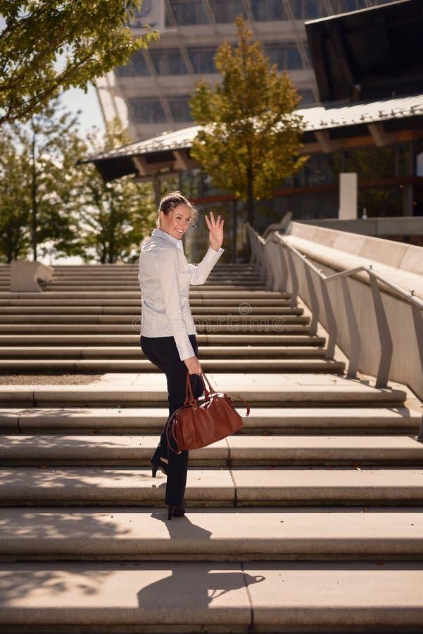 Женщина идя на лестницы развевая рука стоковые изображения