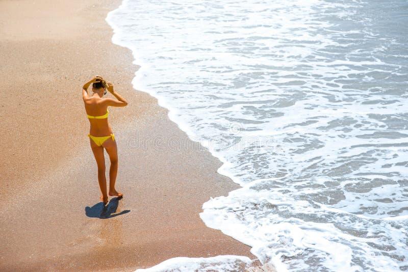 Женщина идя на морское побережье стоковая фотография