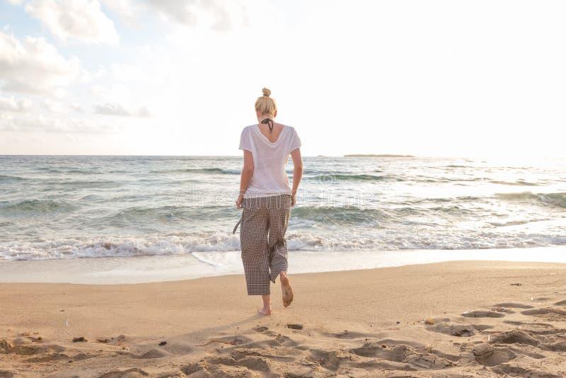 Женщина идя на пляж песка на золотом часе стоковая фотография