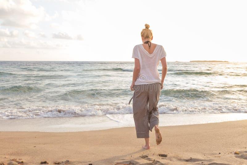 Женщина идя на пляж песка на золотом часе стоковая фотография rf