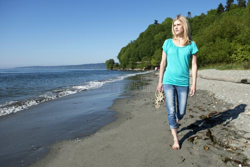 Женщина идя на пляж стоковая фотография