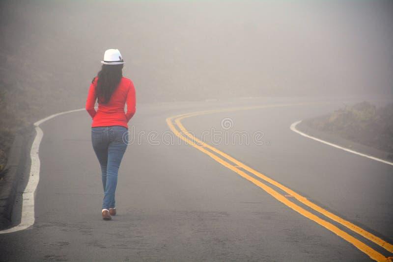 Женщина идя самостоятельно на дорогу в тумане стоковое фото