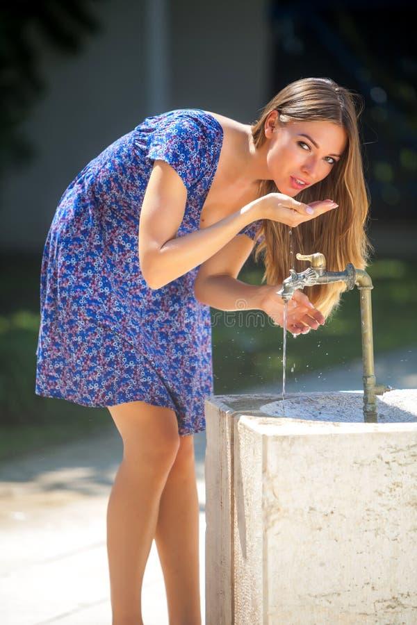 Женщина и faucet стоковая фотография rf
