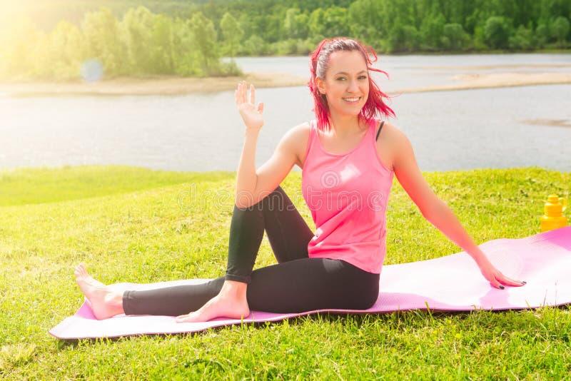 Женщина йоги на зеленой траве над озером Девушка ослабляя в поле в парке Представление йоги йоги практикуя outdoors стоковое фото