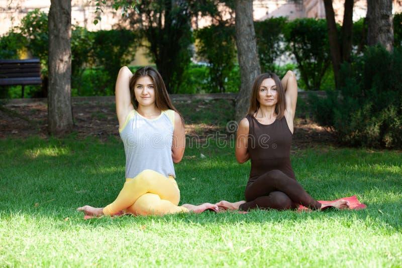 Женщина йоги на йоге зеленой травы внешней Счастливая женщина делая тренировки йоги, размышляет в парке стоковое изображение rf