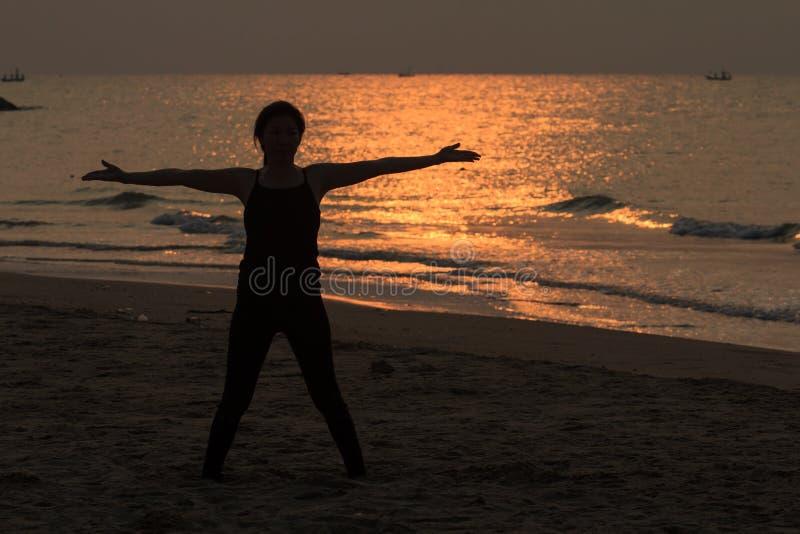 Женщина йоги на красивом пляже на восходе солнца стоковое изображение