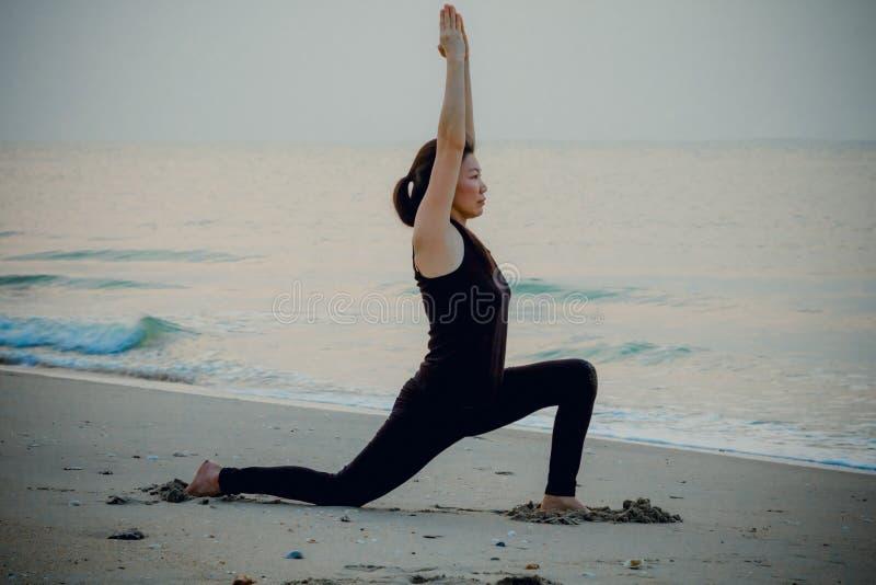 Женщина йоги на красивом пляже на восходе солнца стоковое изображение rf