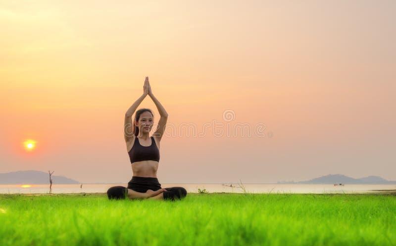 Женщина йоги ослабляет с красивой предпосылкой захода солнца на стоковое изображение rf