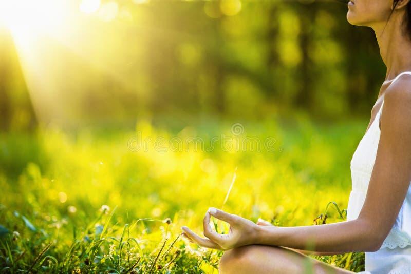 Женщина йоги размышляя на заходе солнца стоковое изображение