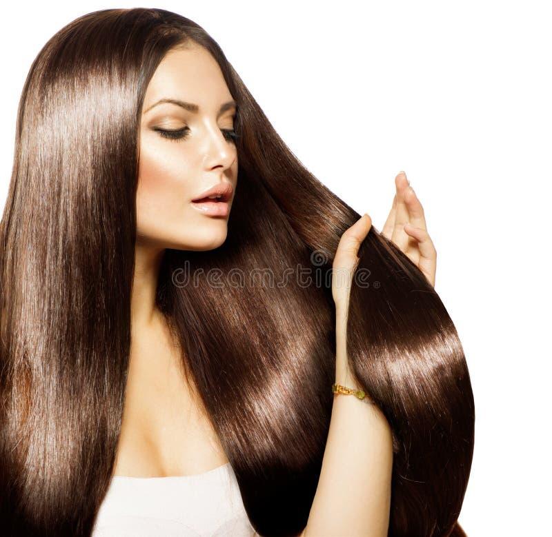 Женщина касаясь ее длинним волосам стоковое изображение