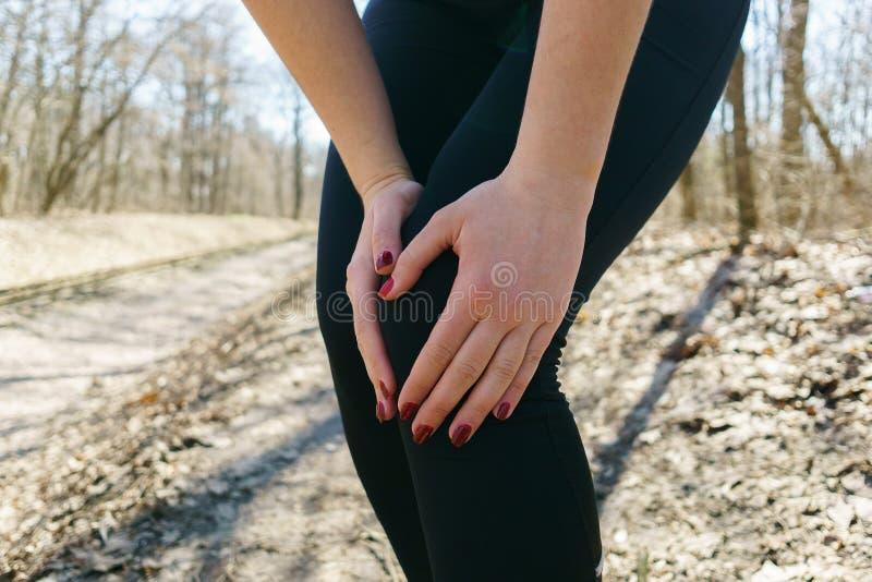 Женщина касаясь ее колену, ушибу спорт на внешний jogging Healt стоковая фотография rf