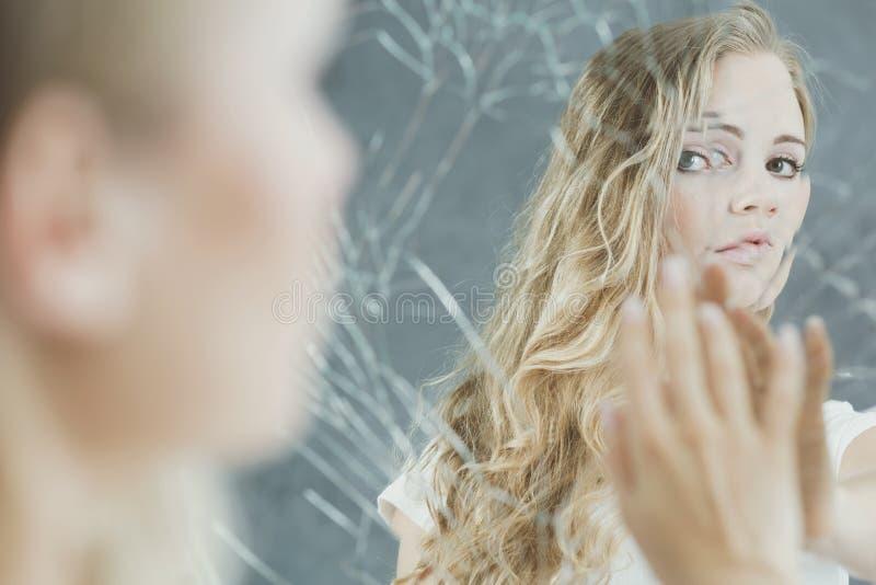 Женщина касаясь ее отражению зеркала стоковые изображения rf