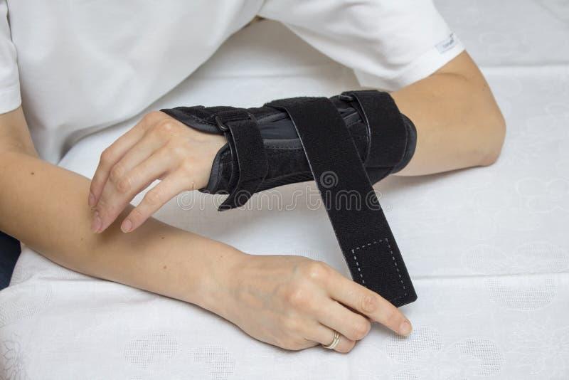 Женщина кладет стабилизатор запястья на ее руку стоковое изображение rf