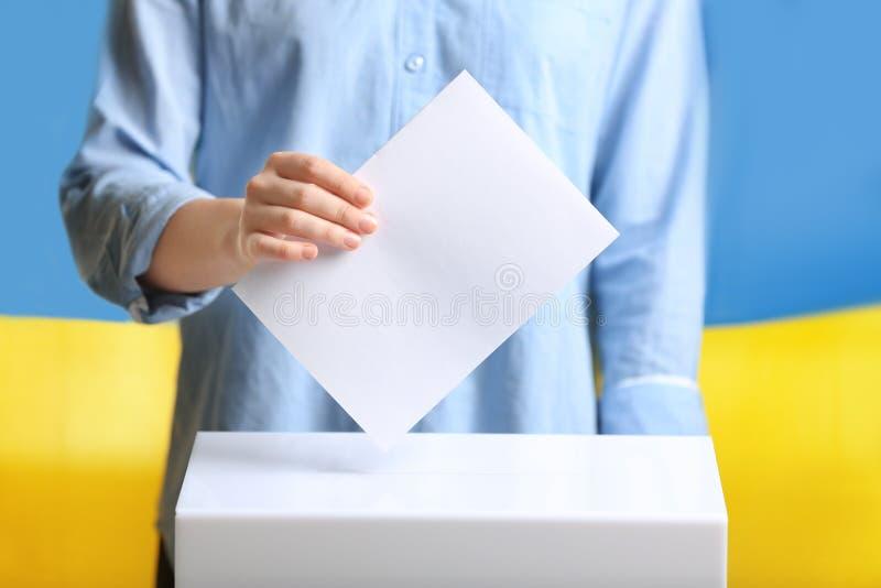 Женщина кладя бумагу голосования в урну для избирательных бюллетеней  стоковая фотография rf