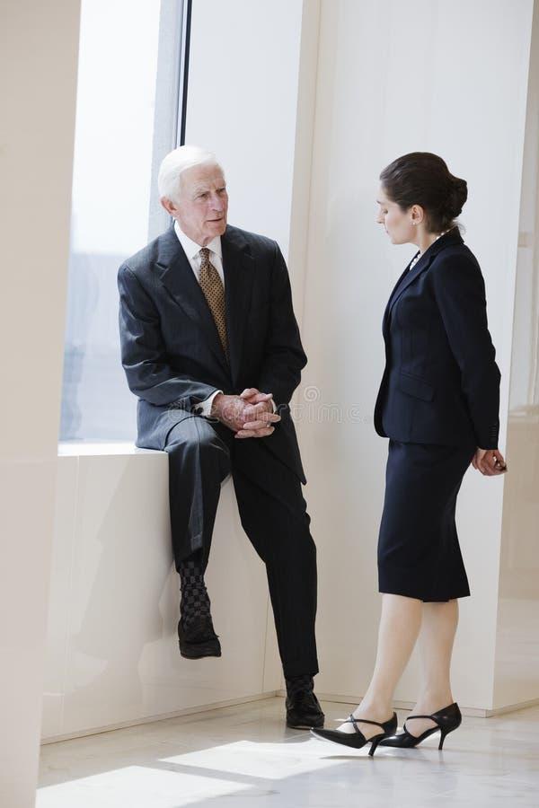 женщина коллегаа бизнесмена старшая говоря стоковое изображение
