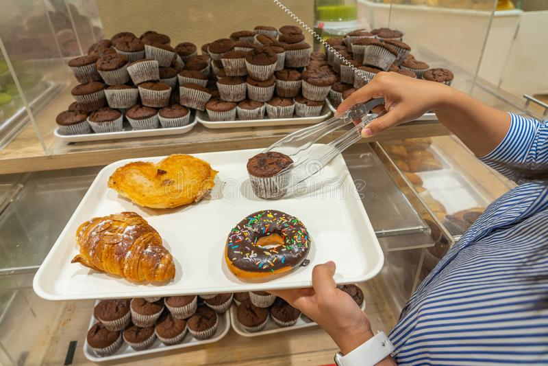 Женщина комплектуя булочку шоколада в ее поднос в пекарне стоковые фотографии rf