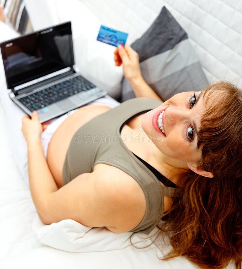 женщина компьтер-книжки кредита карточки супоросая сь стоковое изображение