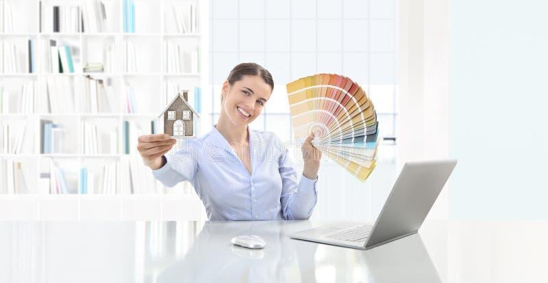 Женщина конструктивной схемы дизайна интерьера усмехаясь показывая цветовую палитру и стоковое фото
