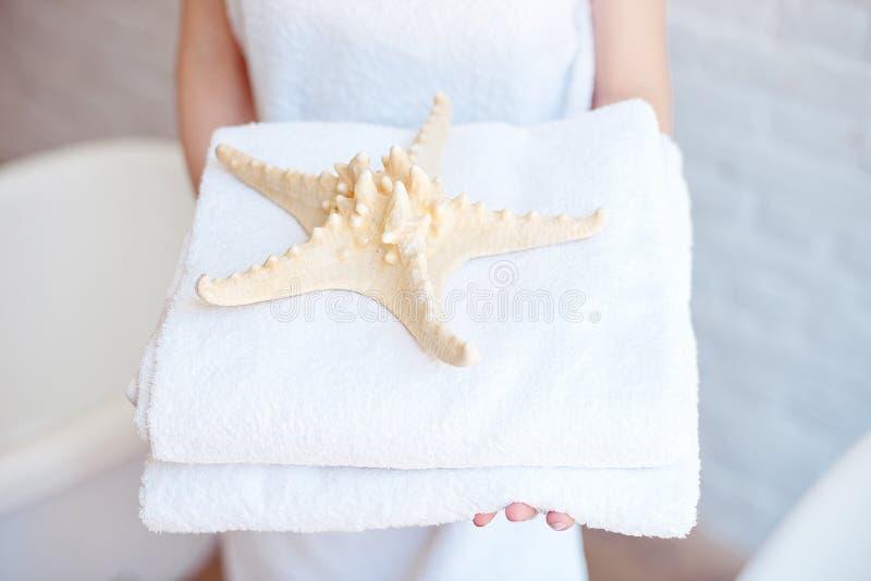 Женщина конца-вверх держа белые полотенца ванны Концепция курорта, гостиниц, курортов стоковые изображения
