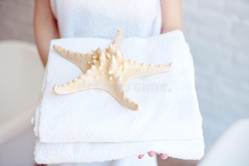 Женщина конца-вверх держа белые полотенца ванны Концепция курорта, гостиниц, курортов стоковые фотографии rf