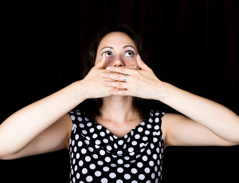 Женщина конца-вверх смотрит прямо в камеру на черной предпосылке Она предусматривала ее рот с ее рукой выражает стоковое изображение
