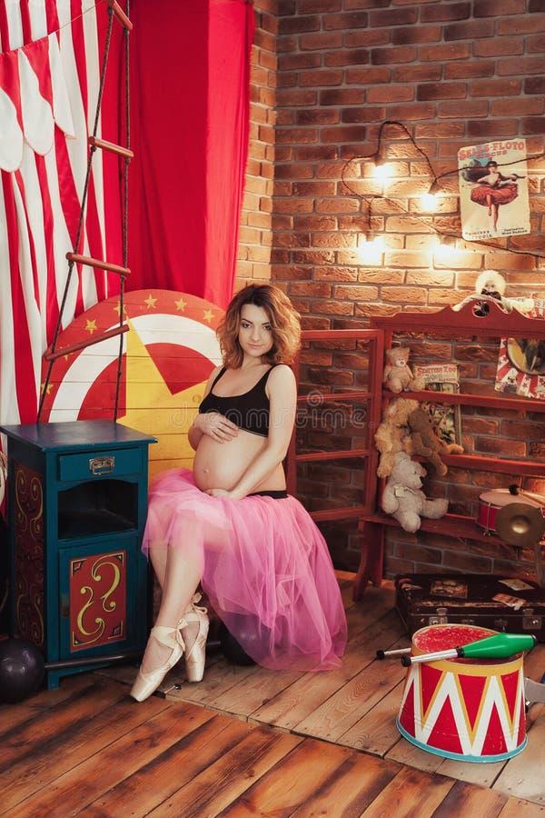Женщина концепции фитнеса и спорта беременности счастливая около розового дерева Сакуры Беременный артист балета на красной кирпи стоковые изображения rf