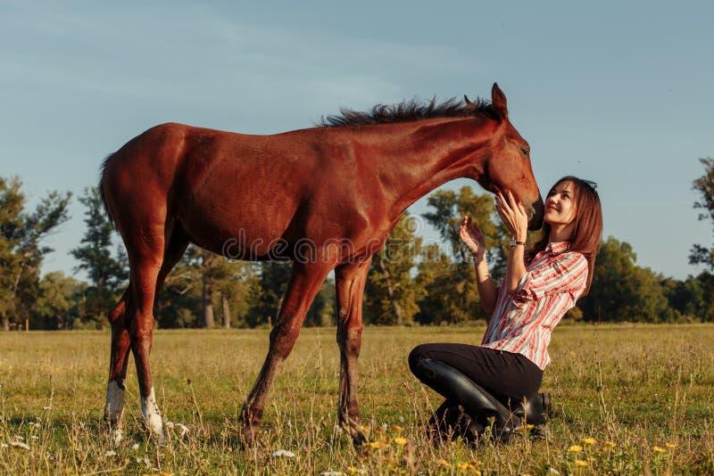 Женщина кормит осленка от ее рук стоковая фотография rf