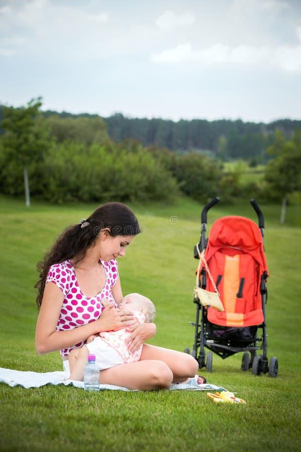 Женщина кормя ее младенца грудью outdoors стоковые изображения