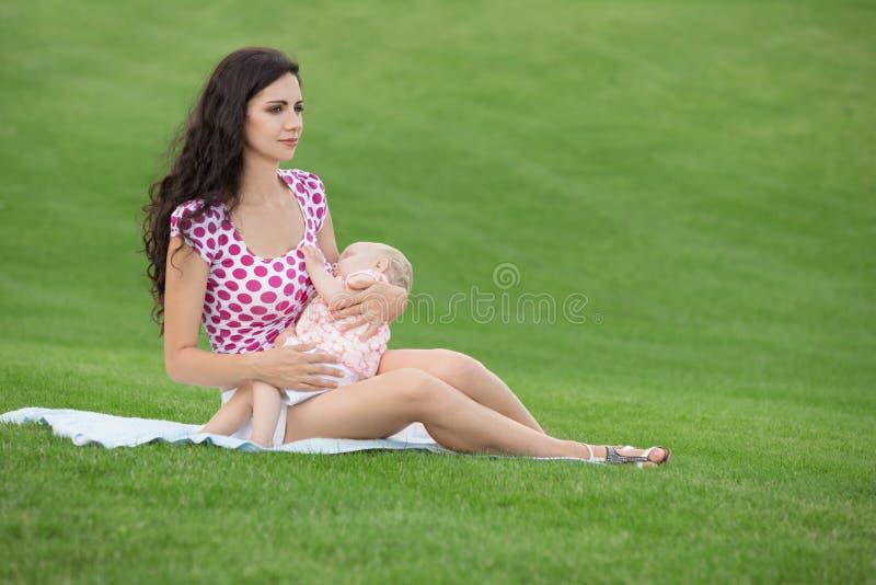 Женщина кормя ее младенца грудью outdoors стоковое фото rf