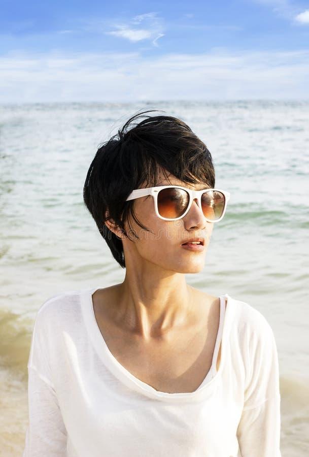 Женщина коротких волос азиатская на пляже стоковая фотография