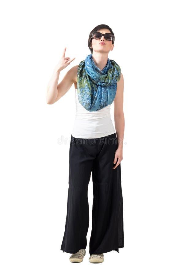 Женщина коротких волос с солнечными очками и шарф показывая рожки дьявола вручают знак стоковые изображения rf