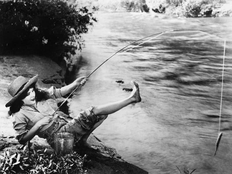 Женщина которая уловила малую рыбу падая над ОН назад (все показанные люди более длинные живущие и никакое имущество не существуе стоковые изображения rf