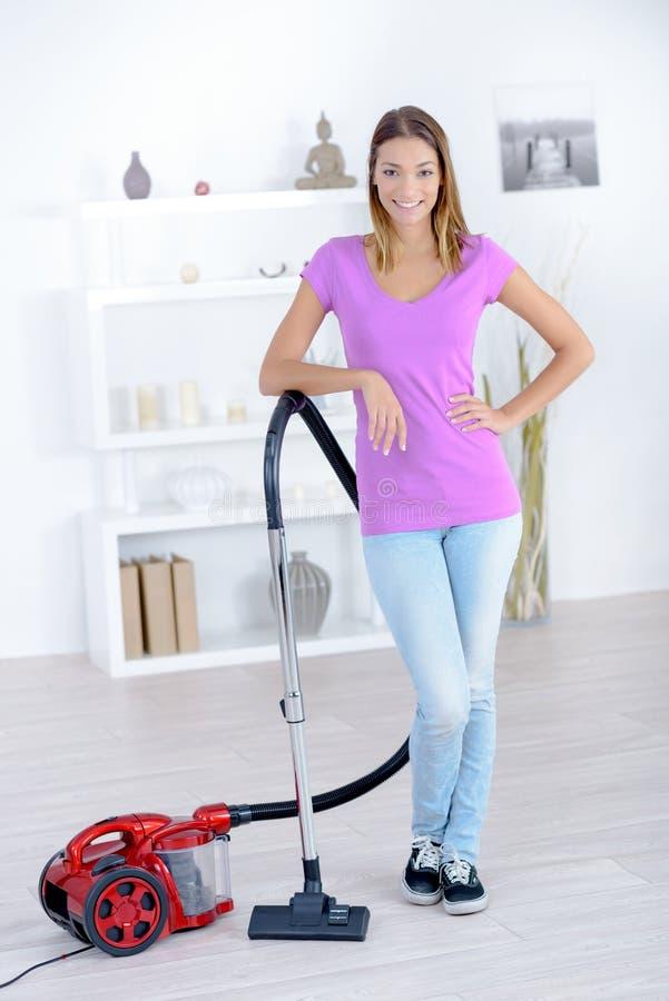 Женщина, который стоят с пылесосом стоковая фотография rf