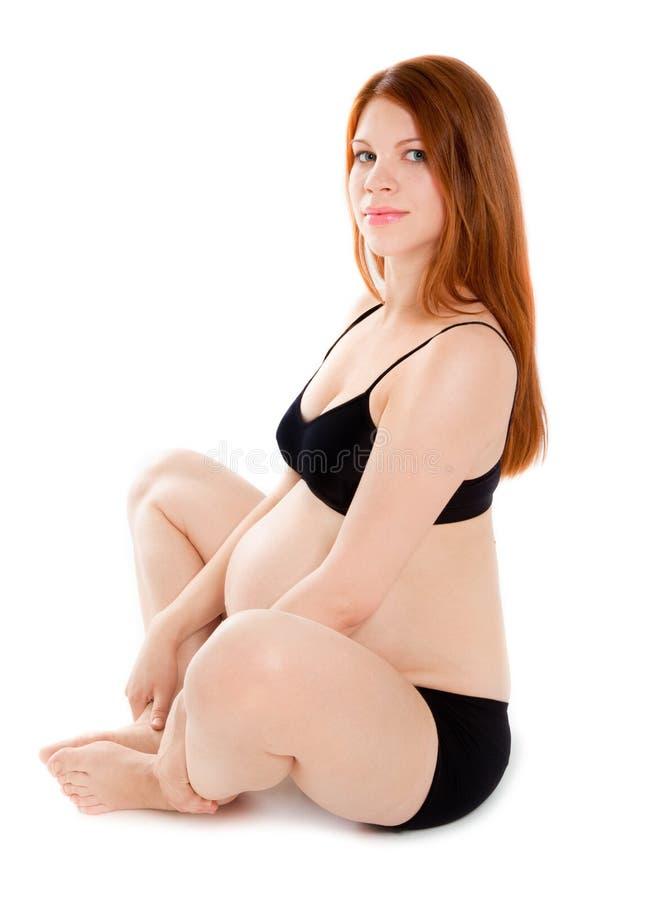 женщина красивейшего пола супоросая сидя стоковое фото