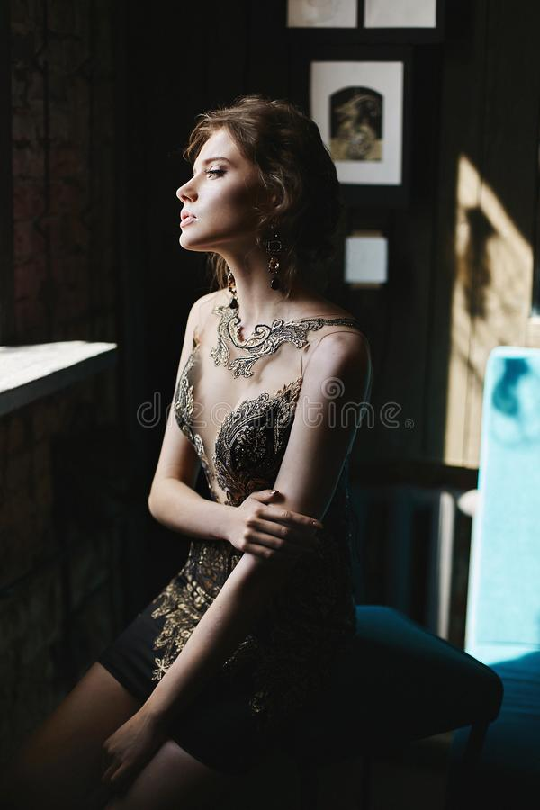 Женщина красивого брюнета модельная с голубыми глазами и идеальным телом в черноте и платье коктейля золота сидят на интерьере ка стоковое изображение