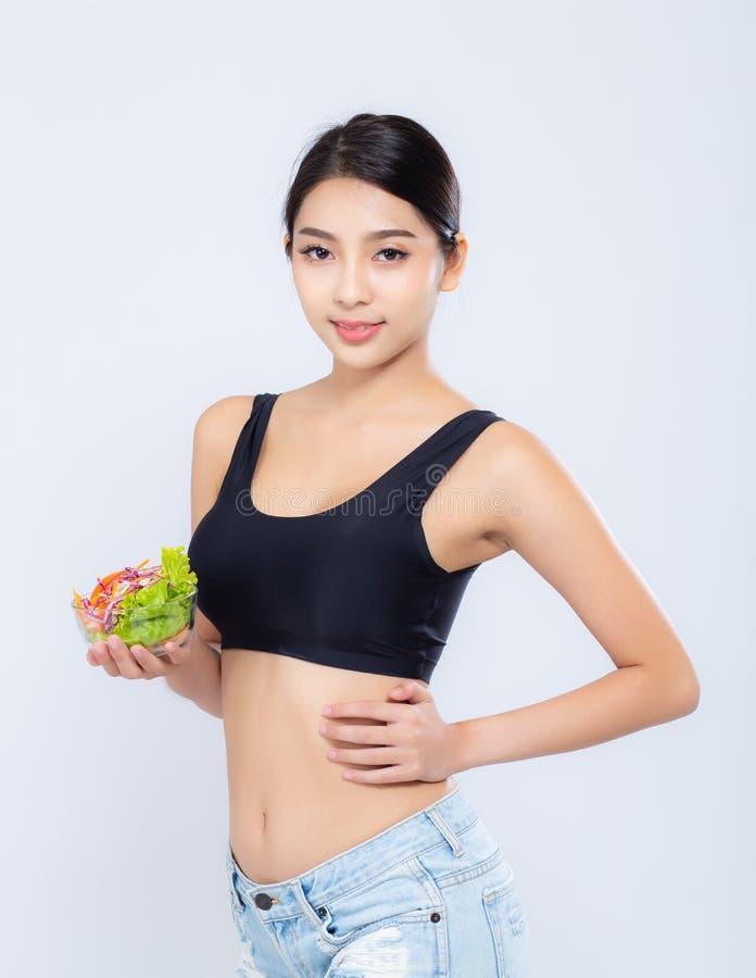 Женщина красивого портрета молодая азиатская усмехаясь держащ еду овоща салата изолированный на белой предпосылке стоковая фотография