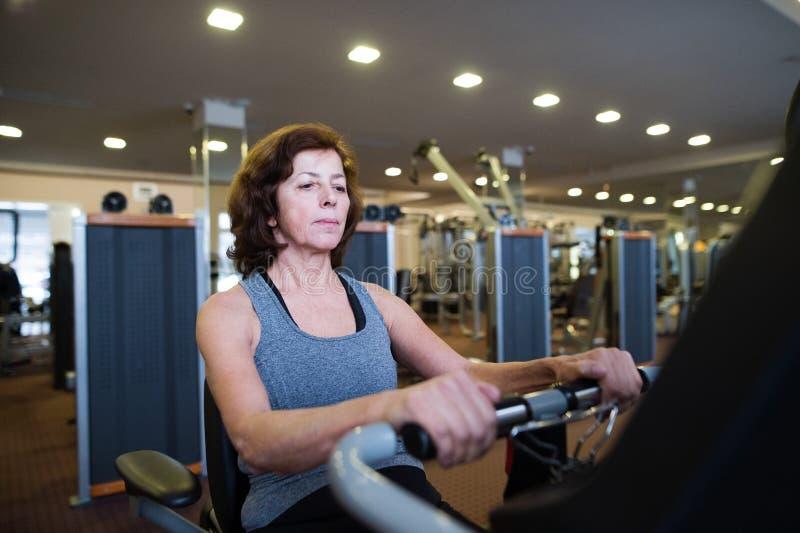 Женщина красивой пригонки старшая в делать спортзала cardio разрабатывает стоковые фото