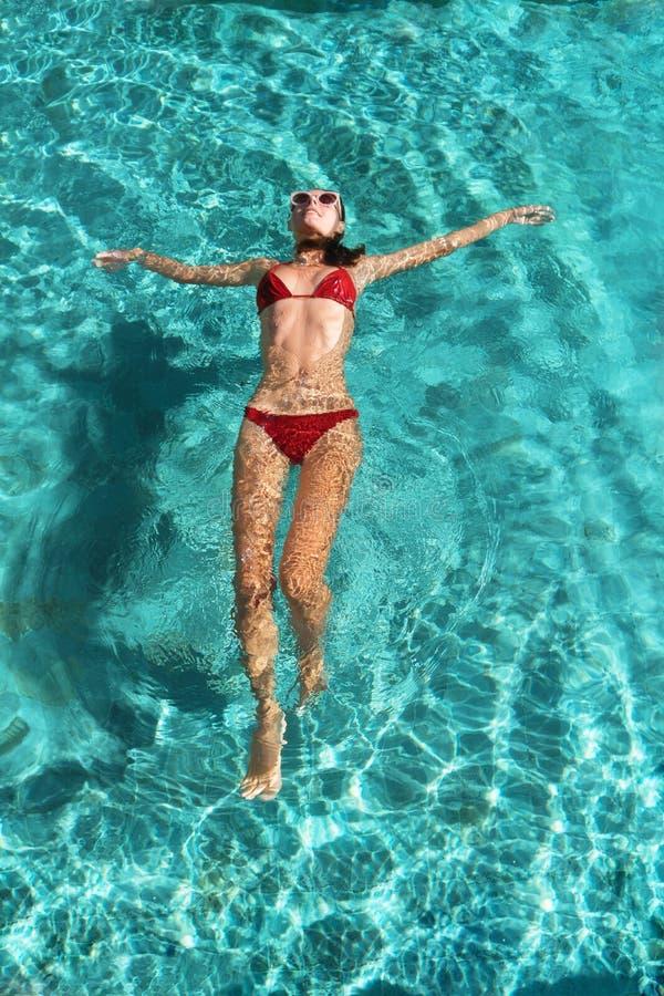 Женщина красивых детенышей тонкая sporty в красном бикини ослабляет на лазурной воде на тропическом острове перемещение карты dub стоковые изображения rf