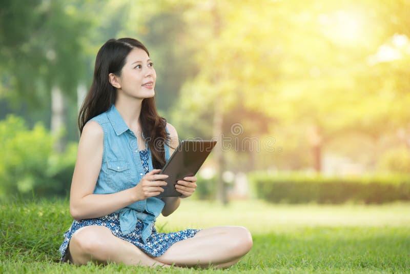 Женщина красоты азиатская используя цифровую таблетку сидя на траве стоковое фото