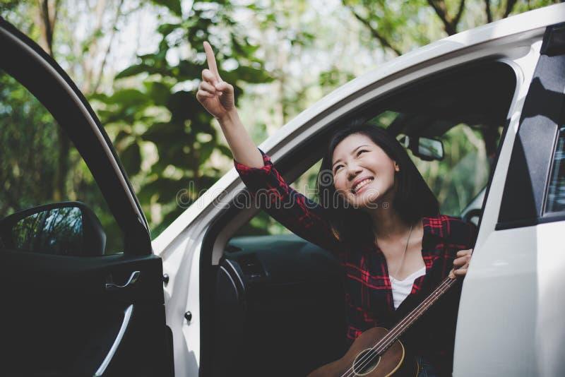 Женщина красоты азиатская указывая и имея потеху на лете outdoors с гавайской гитарой в белом автомобиле Путешествовать концепции стоковые фото