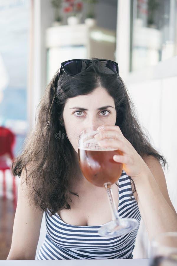 Женщина красоты выпивая чашку пива в ресторане стоковая фотография rf