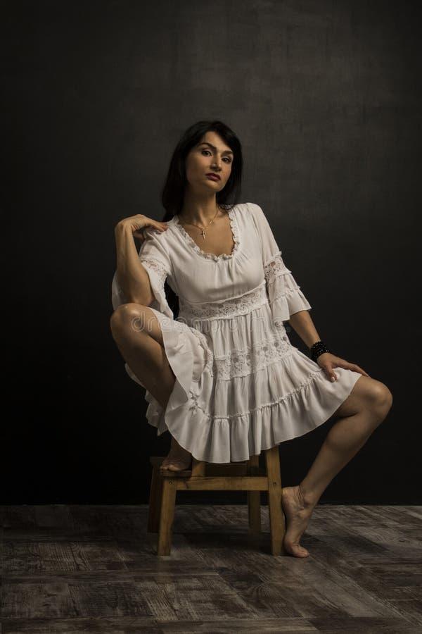 Женщина красоты в белом платье на стуле перед темной стеной стоковые изображения